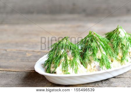 Salad Christmas tree. Salad with meat, mushrooms, cucumbers and eggs decorated with dill. Christmas recipe. Old wooden background with blank copy space for text