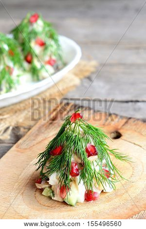Christmas tree salad on a wooden board. Delicious festive salad with meat, champignons, cucumbers and eggs decorated with dill and pomegranate. Christmas food. Old wooden table. Vintage style. Closeup