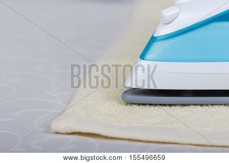 The front part of the modern steam iron, towel on a light gray background.