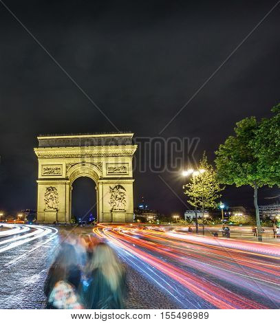 Night time in Arc de Triomphe, car lights and blurred people, long exposure