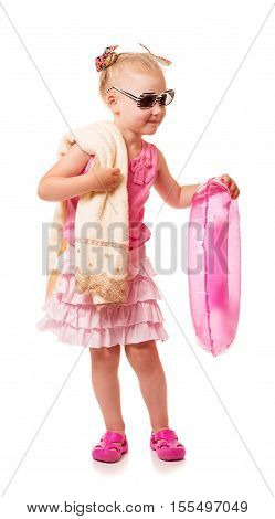 Little blonde girl in sunglasses is holding a towel and inflatable ring isolated on white background.