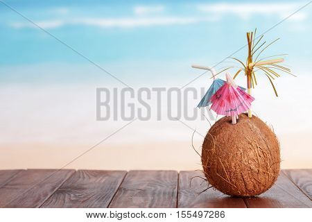 Coconut with straw parasols on the table in front of the sea.