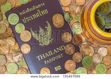 Thai Passport On A Pile Of Coins.