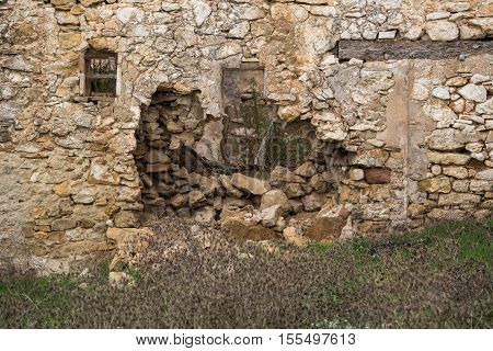 Front view of ruined house stone facade