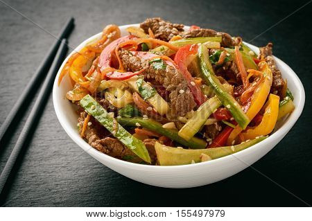 Asian (korean) salad with beef, vegetables and sesame seeds on black board.