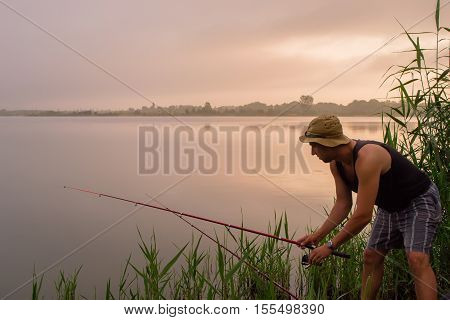 Fisher man fishing with rod on a lake at misty foggy sunrise in the summer