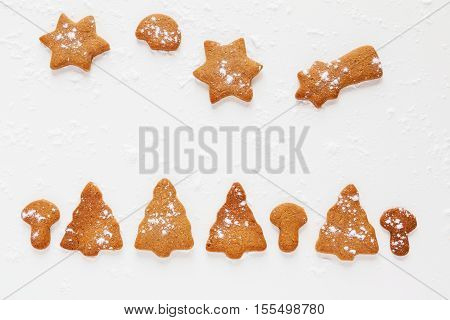 Christmas chocolate and ginger brown cookies in shape of fir-tree star moon and mushrooms. White background with powdered sugar top view.