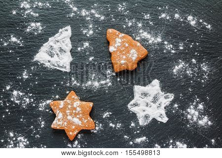 Christmas black background with icing sugar and brown chocolate and ginger cookies in shape of fir-tree and star top view.