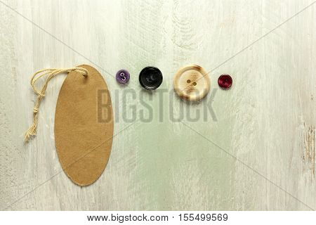 A photo of a kraft cardboard tag with a piece of twine, with retro buttons, shot from above on a light wooden board texture, with copyspace