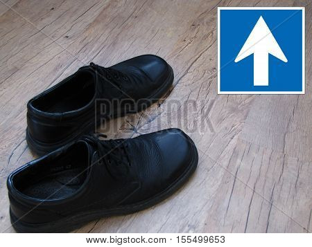 A pair of shoes with a one way road traffic sign in the background.
