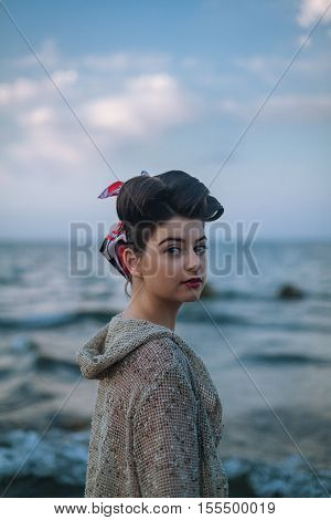 Pinup model with make up and hairstyle on the beach. Beautiful and sexy woman standing into the water on the sea. Relaxing vacation time.