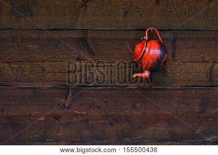 Vintage kettle hanging on a wet wooden wall in a rainy day