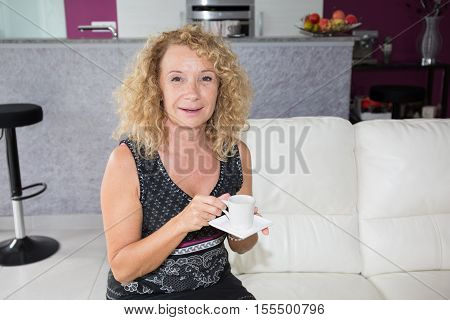 Mature woman at home sipping tea from a cup