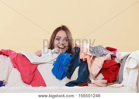 Happy woman behind sofa couch in messy living room. Young girl surrounded by many stack of clothes. Disorder and mess at home.