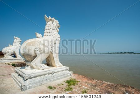 The twin Singha (Lion in Burma style) statue standing behind the Ayeyarwady River, Myanmar.