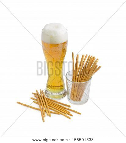Beer glass with lager beer and salty hard crispy mini pretzels shaped as sticks on a light background