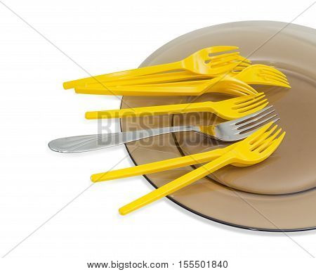 Several yellow plastic disposable forks and one stainless steel fork on a dark glass dish closeup on a light background