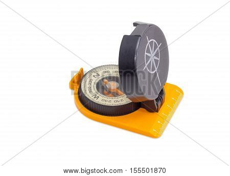 Dry magnetic compass with ruler on a base and image of compass rose on cover on a light background