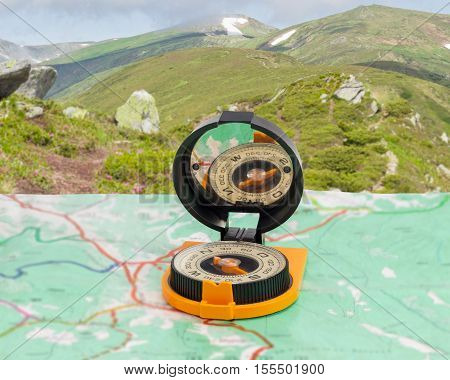 Magnetic compass with mirror of sighting mechanisms on a tourist topographical map against the background of a mountain range