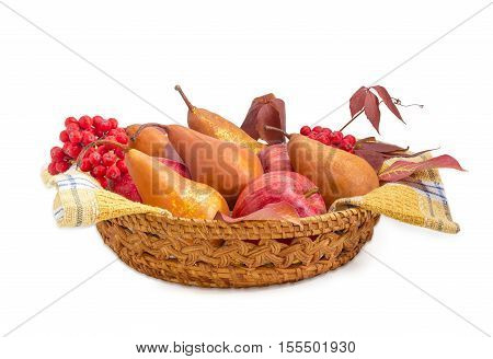Several European pears and red apples on a cotton checkered napkin bunches of rowan and branch of ivy in a small wicker basket on a light background