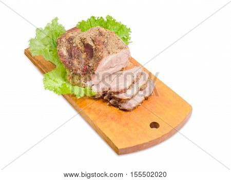 Big piece and several slices of baked pork neck and leaves of a lettuce on wooden cutting board on a light background