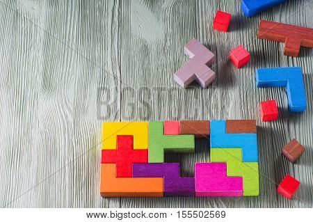 The concept of logical thinking. Geometric shapes on a wooden background. Tetris toy wooden blocks. Logic concept.