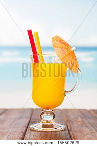 A glass of orange juice with straws and umbrella on a sea background.