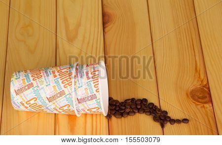 Disposable paper cups and coffee beans on a background of light wood.