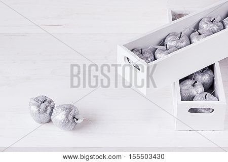 Christmas soft silver decorations in white boxes on a white wooden background. Xmas background.
