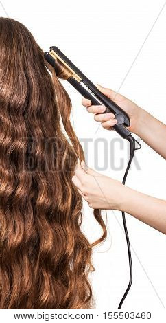 Woman with long hair and hand barber curler isolated on white background. The process of hair curling.