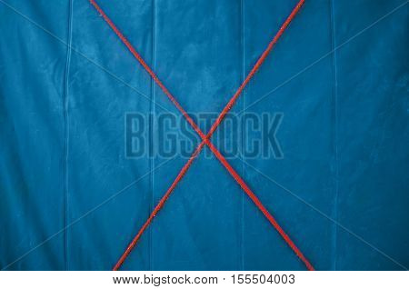 Texture blue tarp with a red cross in the middle of the rope. Blue background.