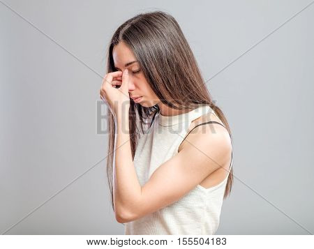 Attractive young woman with a headache pinches the bridge of her nose with a pained expression isolated on gray