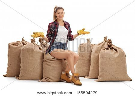 Female farmer sitting on burlap sacks and gesturing with her hands isolated on white background