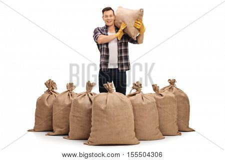 Agricultural worker standing behind burlap sacks and holding a sack on his shoulder isolated on white background