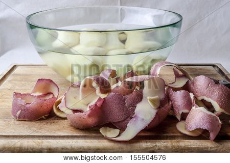 Red potato peels and peeled potatoes in glass bowl with water on wooden cutting board from side