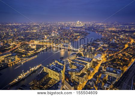 London England - Aerial Skyline view of London. This view includes the Tower of London the iconic Tower Bridge HMS Belfast ship and skyscrapers of Canary Wharf at blue hour