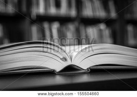 Open Book On The Table In A Library And Bookshelf