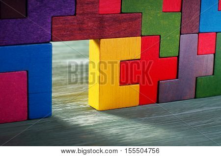 Move beyond. Glowing doorway colorful wall of wooden puzzles. Move beyond meaning or definition.