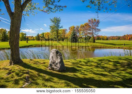 Small pond with a clay bottom is surrounded by reeds.  Concept of recreational tourism. Shining sunny day in French Canada. Green grass lawn and trees