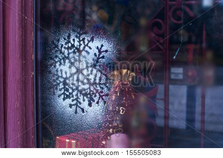 Christmas decoration snowflakes sputtering on window glass.