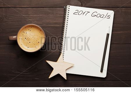 Cup of coffee and notebook with goals for 2017 on wooden table from above. Planning and motivation for the new year concept.