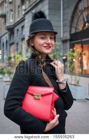 Young beautiful girl with red bag wearing a black hat and leather coat near the wall of the shopping center