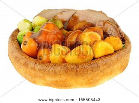 Roast beef meal in a Yorkshire pudding with roasted potatoes and vegetables isolated on a white background