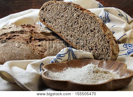 Sliced whole grain bread and a wooden cup of flour on a fabric cover.