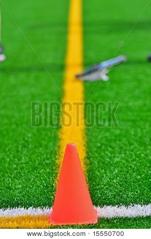 Cone & lacrosse stick on a turf field