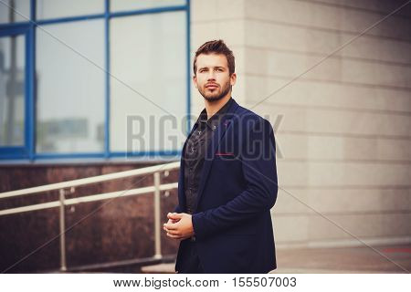 handsome successful manager in a suit. Portrait of a businessman near the office