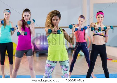 Group of women exercising with dumbbell in gym
