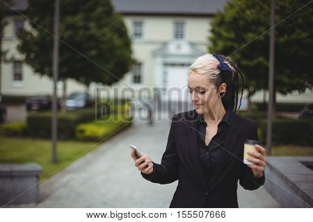 Businesswoman using mobile phone while holding disposable coffee cup in office campus