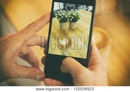 Young girl is taking photo of her coffee