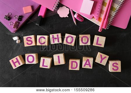 Words SCHOOL HOLIDAYS and stationery set on blackboard background